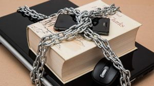 Book, laptop and cell phone wrapped in chains
